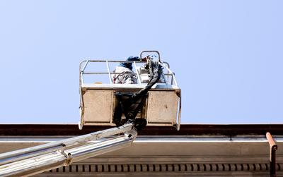 Roofer in Boom Truck